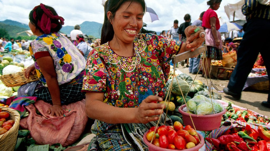 A local Mayan woman sells produce at a market © | Courtesy of NatGeo