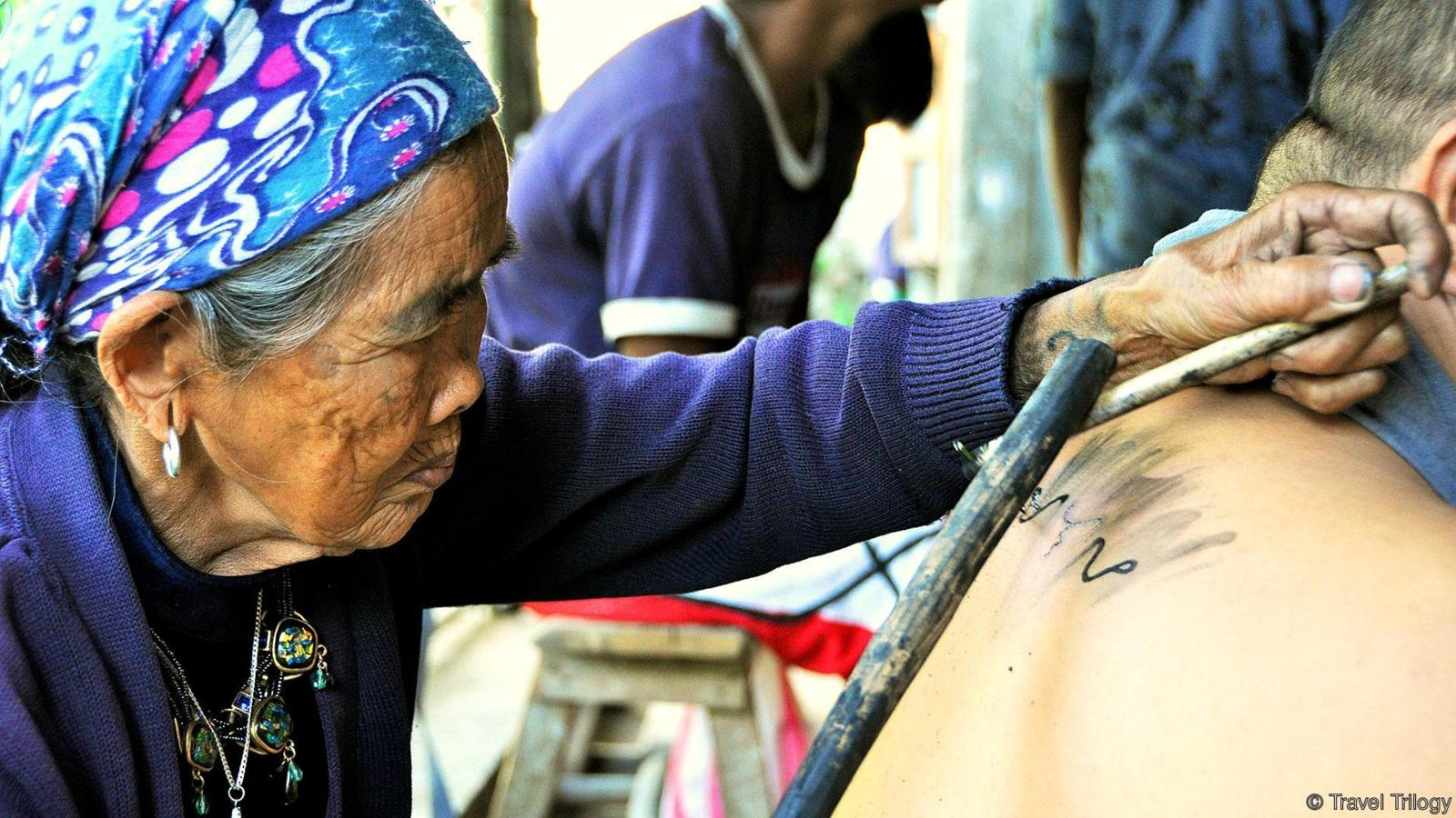 Apo Whang-Od giving a tattoo to a traveler © | Travel Trilogy