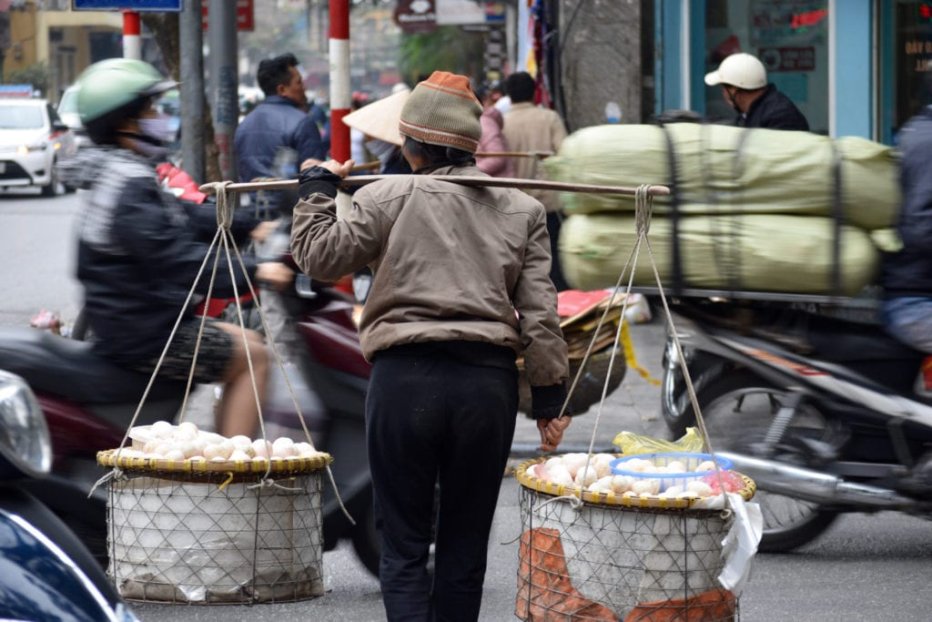 A street vendor crosses a busy avenue in Hanoi © | Nikki Vargas