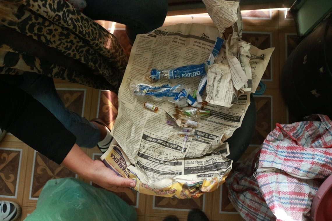 Ex-user and Dristi volunteer, Punam Rai, in the Dristi office in Dharan shows drug paraphernalia © | Jenna Kunze