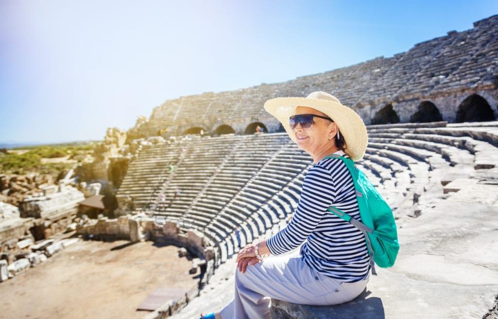 Mature beautiful woman traveler, sits on the steps of the amphitheater in Greece | © Olesya Kuznetsova