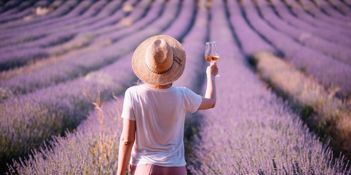 A woman raises a glass of rose in France | © Anastasia Ness/Shutterstock