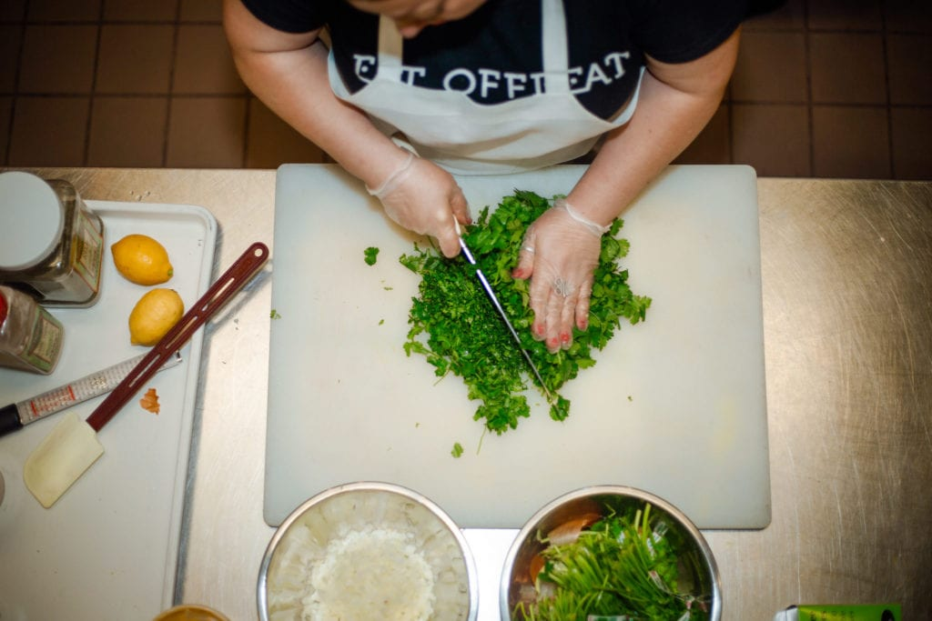 Resettled refugee, Chef Nasrin prepares a dish at the Eat Offbeat kitchen | © Phil Provencio/Unearth Women