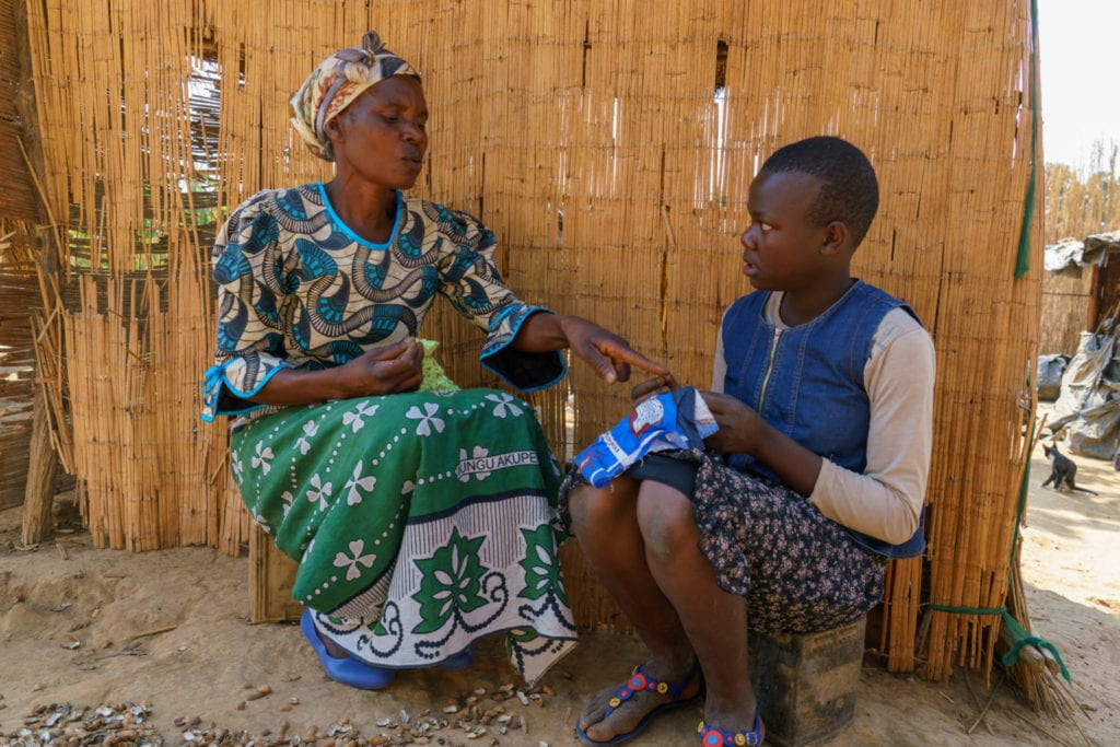 Elizerbeth, 54, teaching her grand-daughter, Mary how to make a sanitary cloth locally known as nyanda | © WaterAid/ Dennis Lupenga