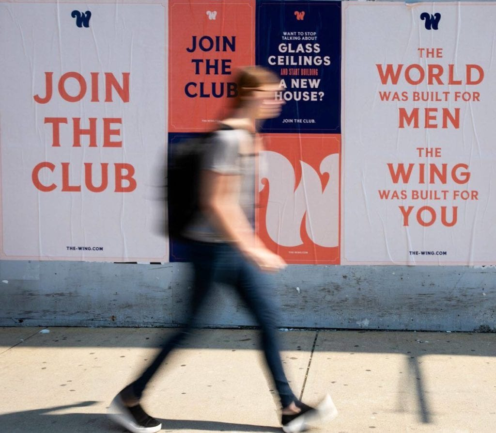 A woman walks past The Wing's ad campaign | © The Wing Facebook Page