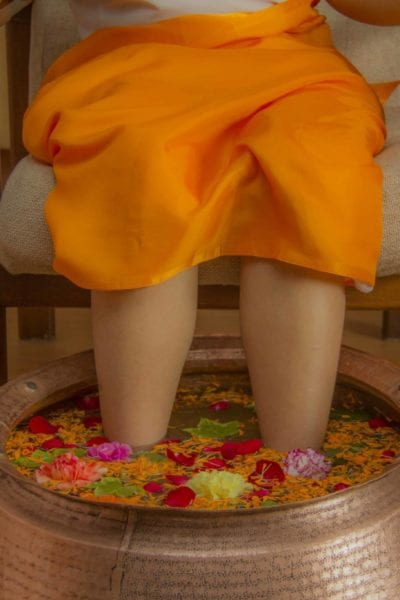 A client receives a flower-filled foot bath treatment. | © Moksha Ayurveda & Panchakarma Center