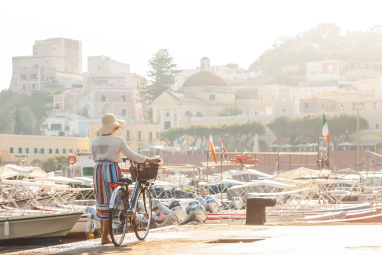 Young woman with bike at Ponza Island harbor pier in Italy | © WineDonuts/Shutterstock