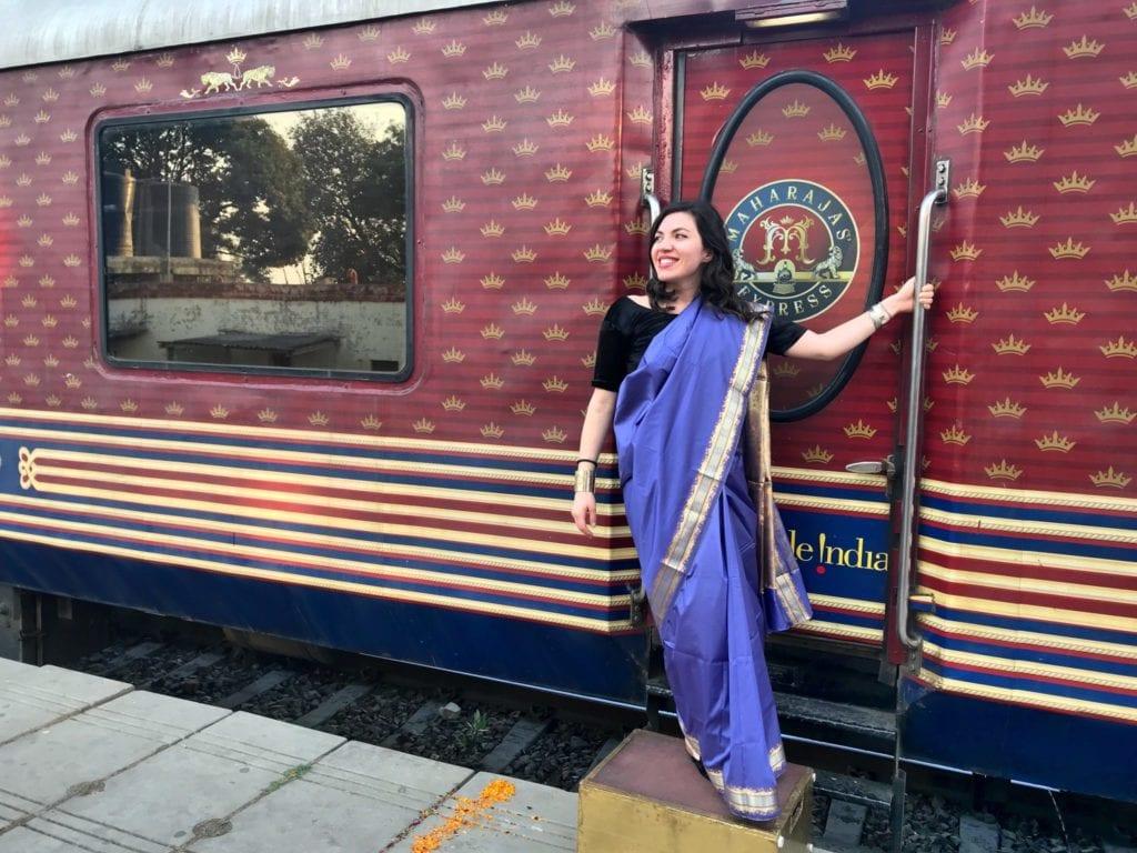 The author poses outside India's Maharaja Express | © Nikki Vargas