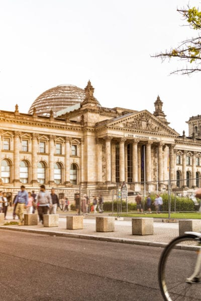 A local Berlin woman bikes past the famous Reichstag building | © Shutterstock