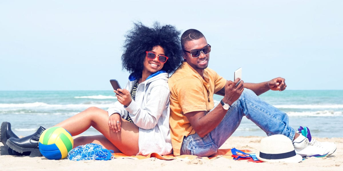 A happy young couple poses on the beach | © Akhenaton Images