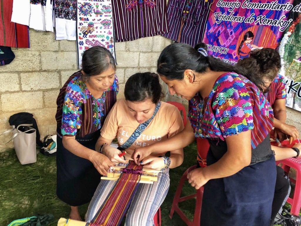 The women of the Consejo de Tejedoras de Santo Domingo Xenacoj show the author how to weave using a loom | © Nikki Vargas/Unearth Women
