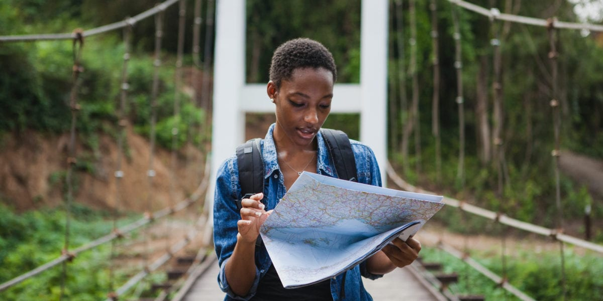 A solo black female traveler looks at a map | © Shutterstock